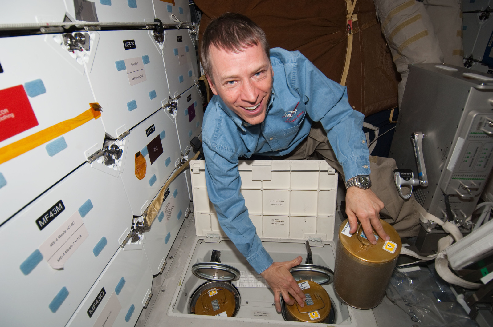 S125E009752 - STS-125 - STS-125 Pilot Johnson replaces LiOH Cannisters on the Shuttle Atlantis Middeck