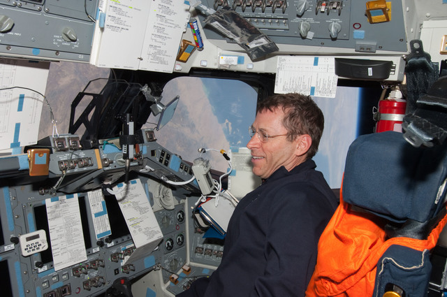 S125E013887 - STS-125 - STS-125 Pilot Gregory C. Johnson works on the Flight Deck