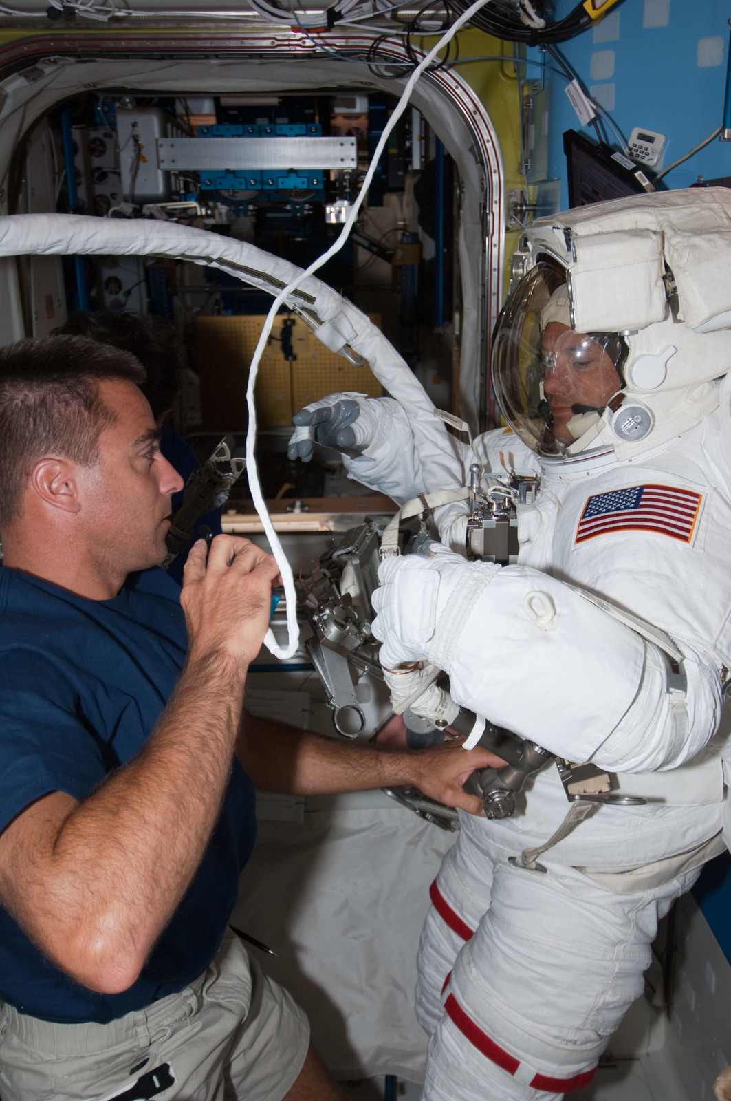 S127E007045 - STS-127 - Cassidy assists Marshburn with his EMU during STS-127 / Expedition 20 Joint Operations
