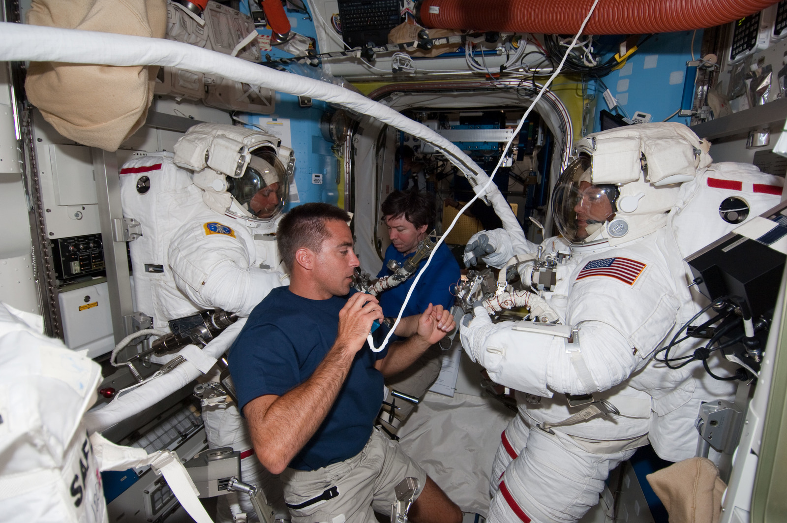 S127E007048 - STS-127 - Cassidy and Barratt assists Marshburn and Wolf with their EMUs during Joint Operations