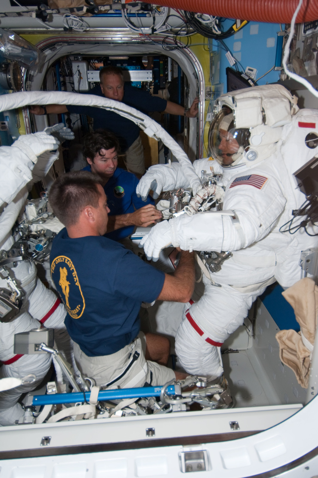 S127E007054 - STS-127 - Cassidy and Barratt assists Marshburn with his EMU during Joint Operations