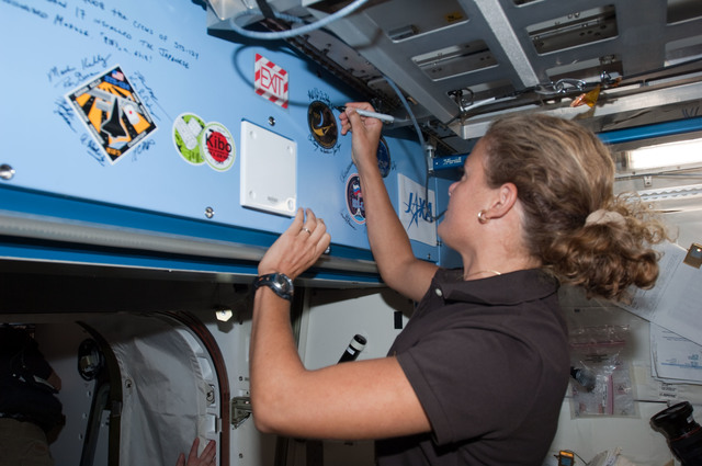 S127E008614 - STS-127 - Payette signs mission decal in the JEM during Joint Operations