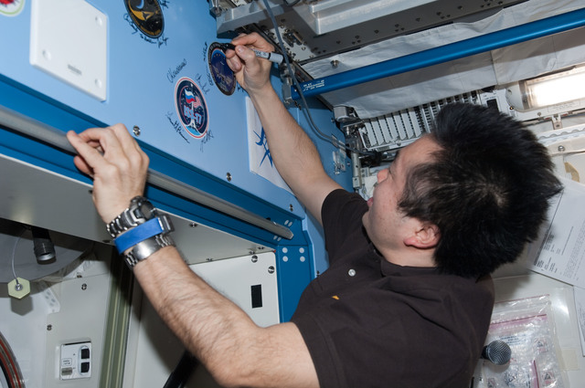 S127E008630 - STS-127 - Wakata signs mission decal in the JEM during Joint Operations