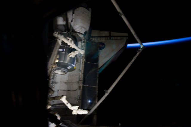 s133E007483 - STS-133 - Dark view of PMM being transferred to Node 1