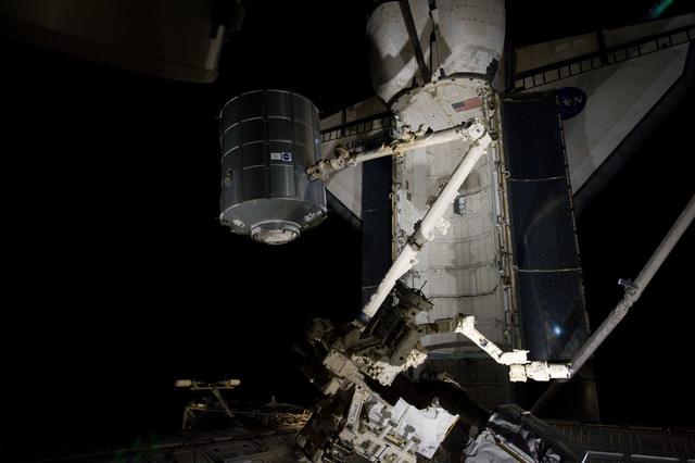 s133E007502 - STS-133 - Dark view of PMM being transferred to Node 1