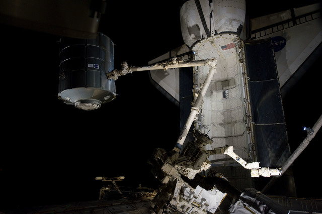 s133E007525 - STS-133 - Dark view of PMM being transferred to Node 1