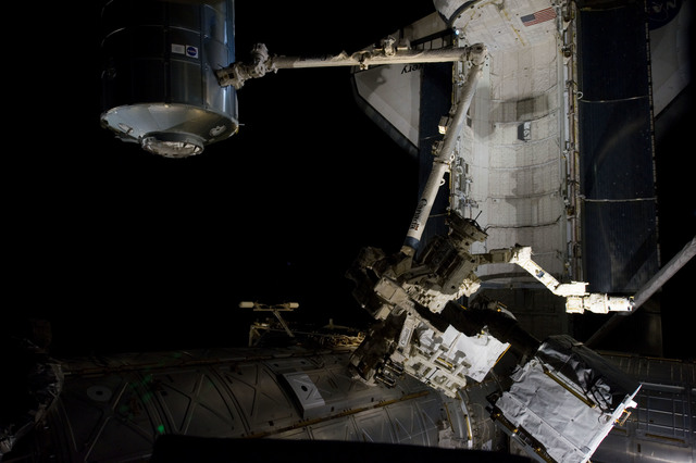 s133E007534 - STS-133 - Dark view of PMM being transferred to Node 1