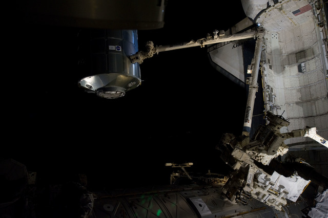 s133E007540 - STS-133 - Dark view of PMM being transferred to Node 1