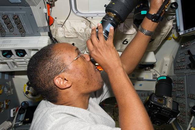 s133E013151 - STS-133 - Drew at aft flight deck windows