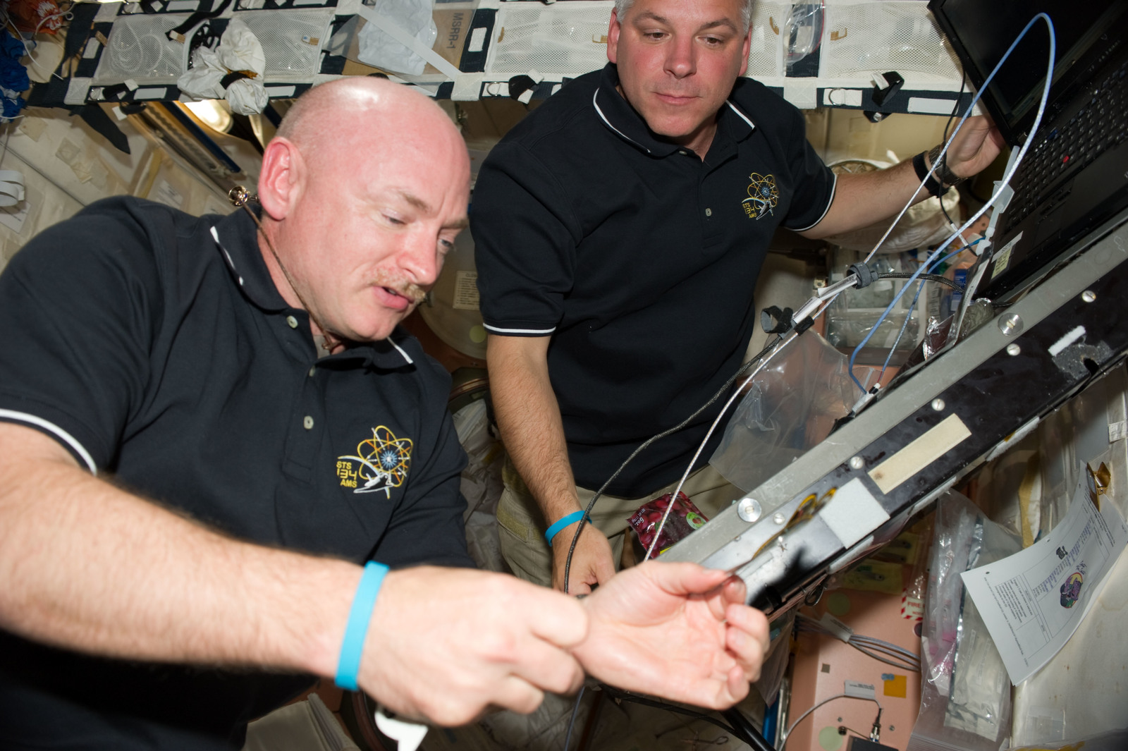 S134E008423 - STS-134 - STS-134 Crew Members add Mission Sticker to Node 1 Panel