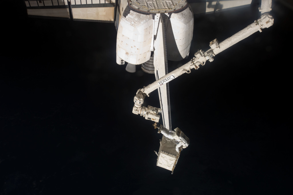 S135E007511 - STS-135 - Garan transfers Pump Module during EVA 1
