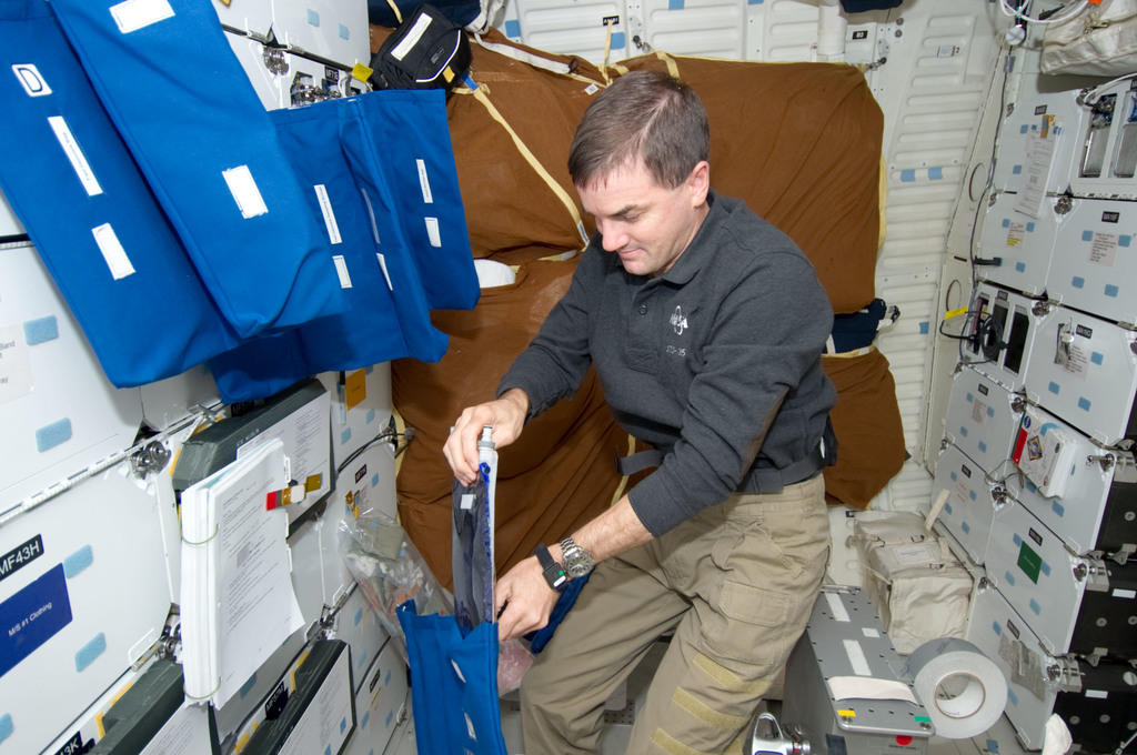 S135E011573 - STS-135 - Walheim works with Forward Osmosis Bag Payload on Middeck