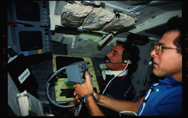 S35-16-002 - STS-035 - STS-35 Commander Brand in sleep station compartment on OV-102's middeck