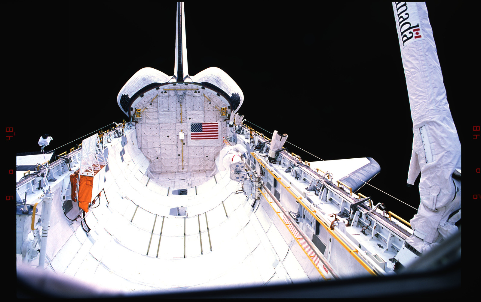 S37-33-021 - STS-037 - Astronauts in EMU's in the payload bay