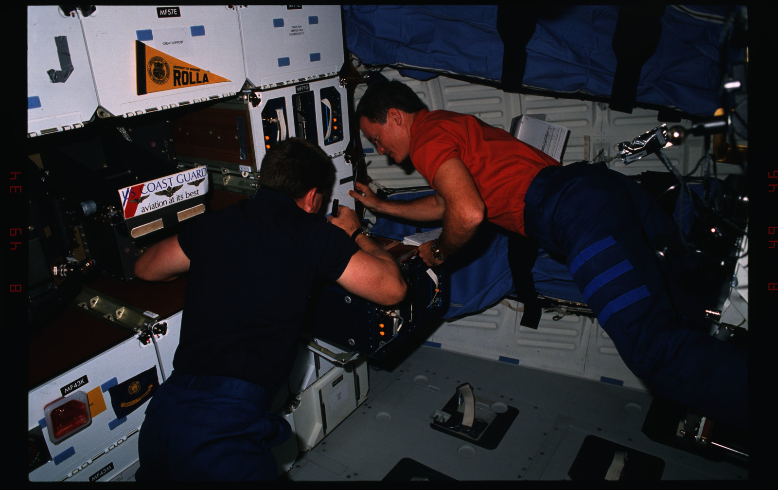 S41-06-021 - STS-041 - Melnick & Akers work with the Physiological Systems Experiment on Discovery
