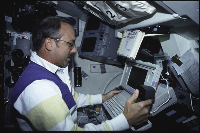 S43-14-035 - STS-043 - STS-43 MS Adamson conducts DTO 1208 using laptop on OV-104's flight deck