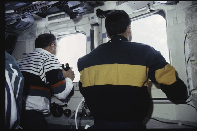 S43-38-009 - STS-043 - STS-43 Low and Adamson look through the windows on OV-104's flight deck