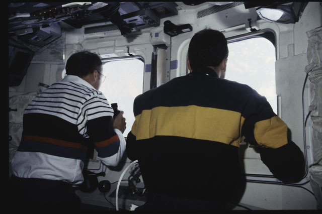 S43-38-010 - STS-043 - STS-43 Low and Adamson look through the windows on OV-104's flight deck