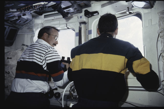 S43-38-011 - STS-043 - STS-43 Low and Adamson look through the windows on OV-104's flight deck