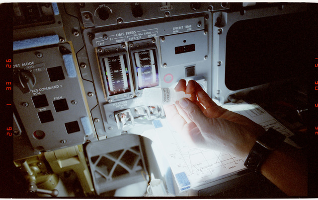 S45-20-025 - STS-045 - STS-45 crewmember holds various items