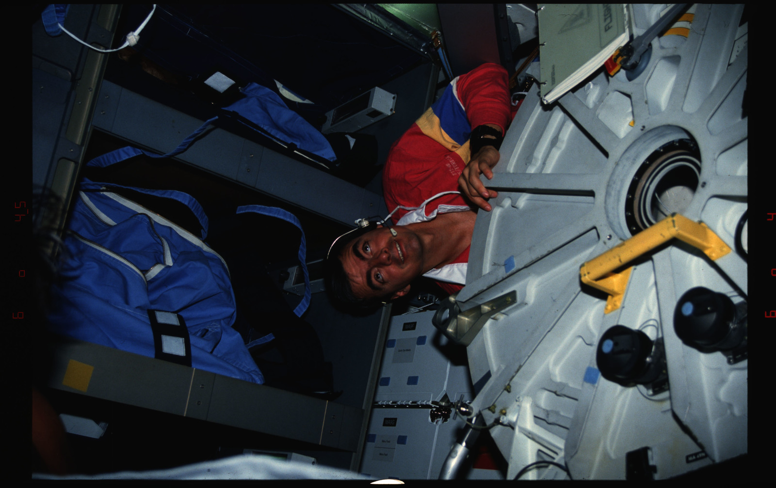 S46-04-009 - STS-046 - Pilot Allen peers into the OV-104 middeck from behind the Airlock hatch