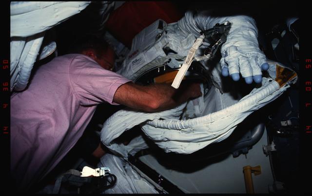 S48-04-022 - STS-048 - Buchli unpacks an EMU in the airlock