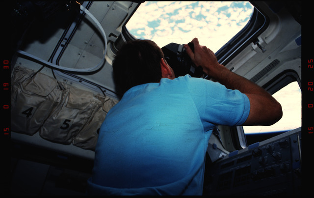 S48-07-033 - STS-048 - STS-48 crew take photos from the aft flight deck windows