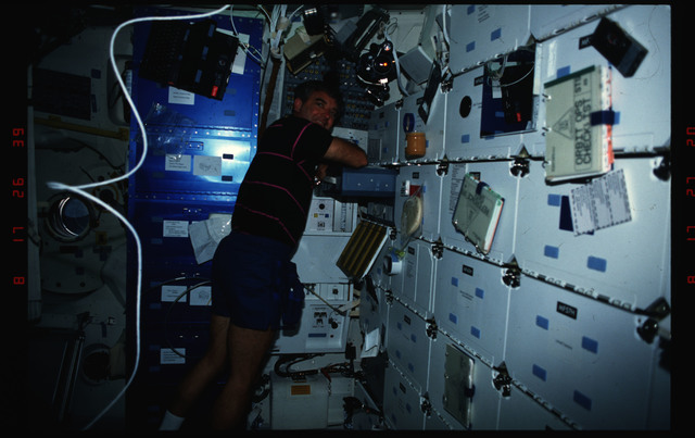 S49-03-018 - STS-049 - Crew members perform inflight maintenance tasks and experiments on middeck