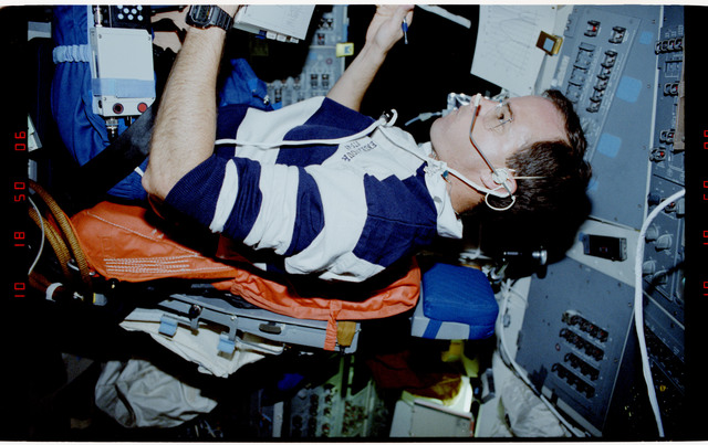S49-20-022 - STS-049 - Crewmember, sitting in the pilot's chair, reviewing a procedures document.