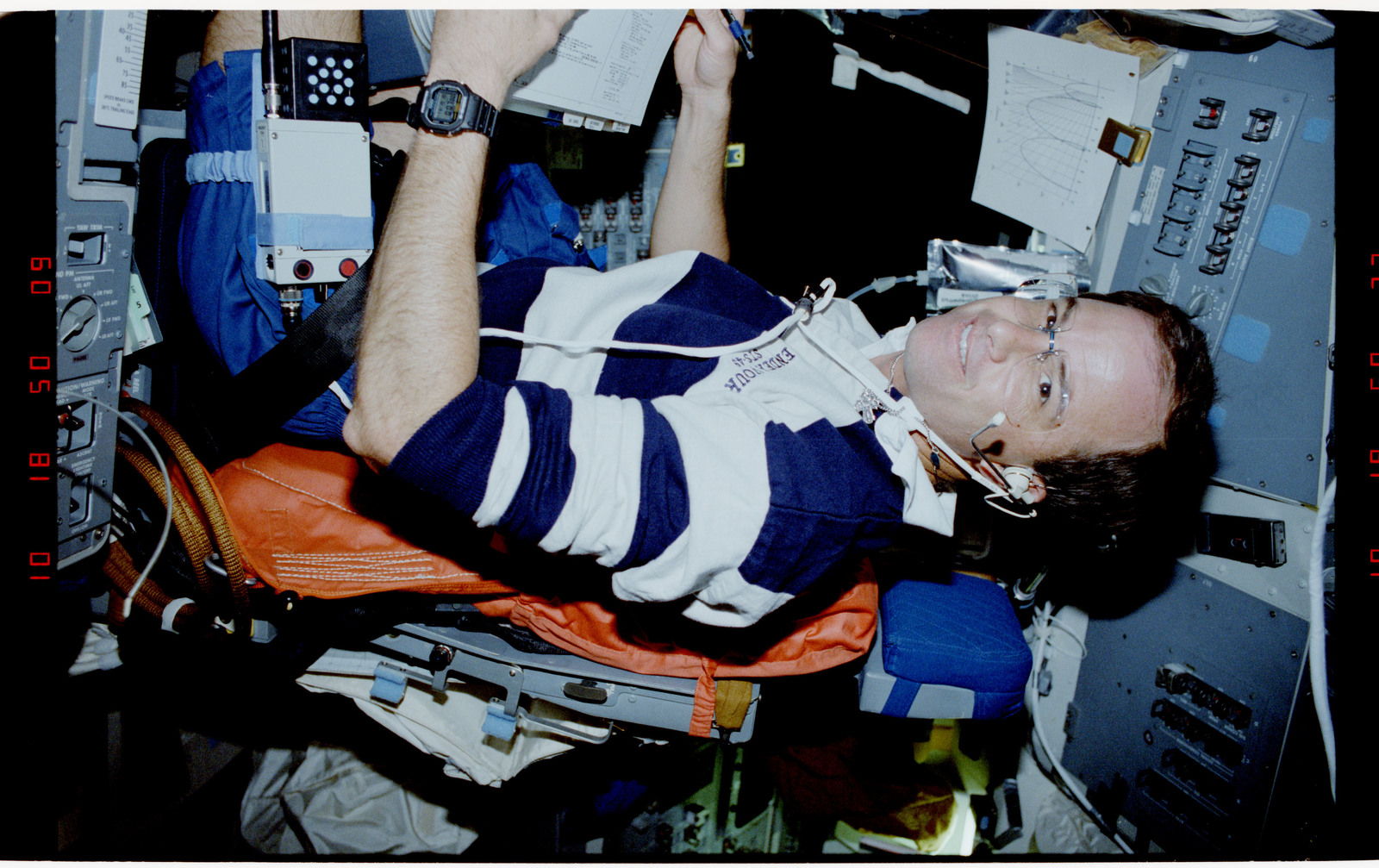 S49-20-023 - STS-049 - Crewmember, sitting in the pilot's chair, reviewing a procedures document.