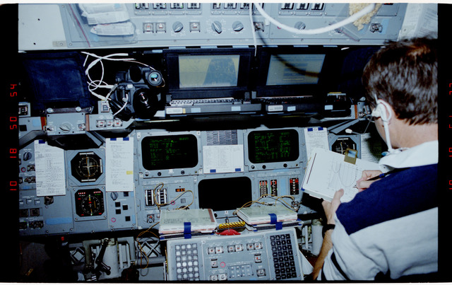 S49-20-026 - STS-049 - Crewmember, sitting in the pilot's seat, reviewing a procedures document.