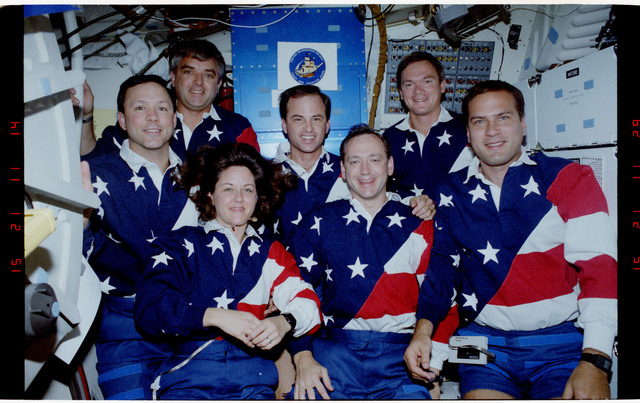 S49-21-004 - STS-049 - Mid deck in orbit crew portraits taken in both flag motif and yellow shirts.