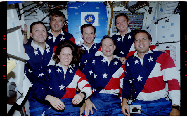 S49-21-006 - STS-049 - Mid deck in orbit crew portraits taken in both flag motif and yellow shirts.