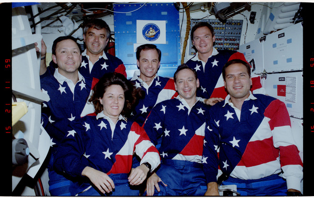 S49-21-007 - STS-049 - Mid deck in orbit crew portraits taken in both flag motif and yellow shirts.