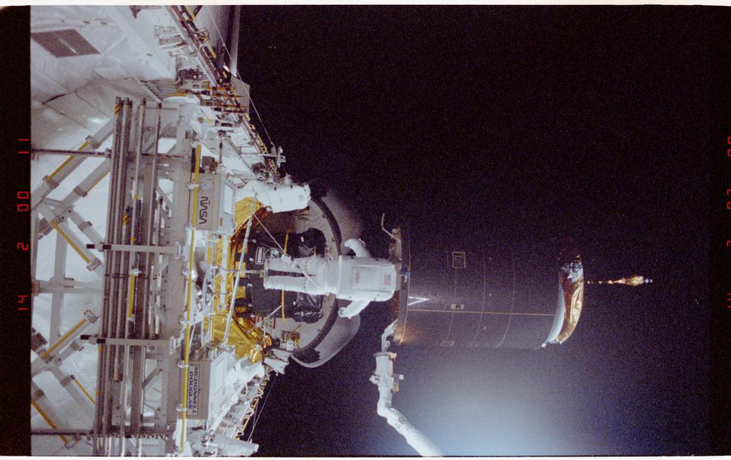 S49-211-015 - STS-049 - Three Mission Specialist EVA manual INTELSAT capture.
