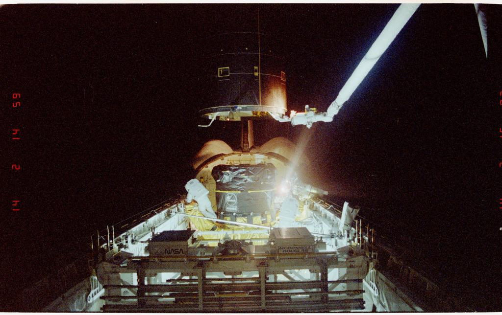 S49-211-023 - STS-049 - Three Mission Specialist EVA manual INTELSAT capture.