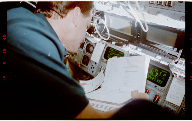 S49-36-036 - STS-049 - Crewmember reviewing a procedures document in the fwd flight deck.