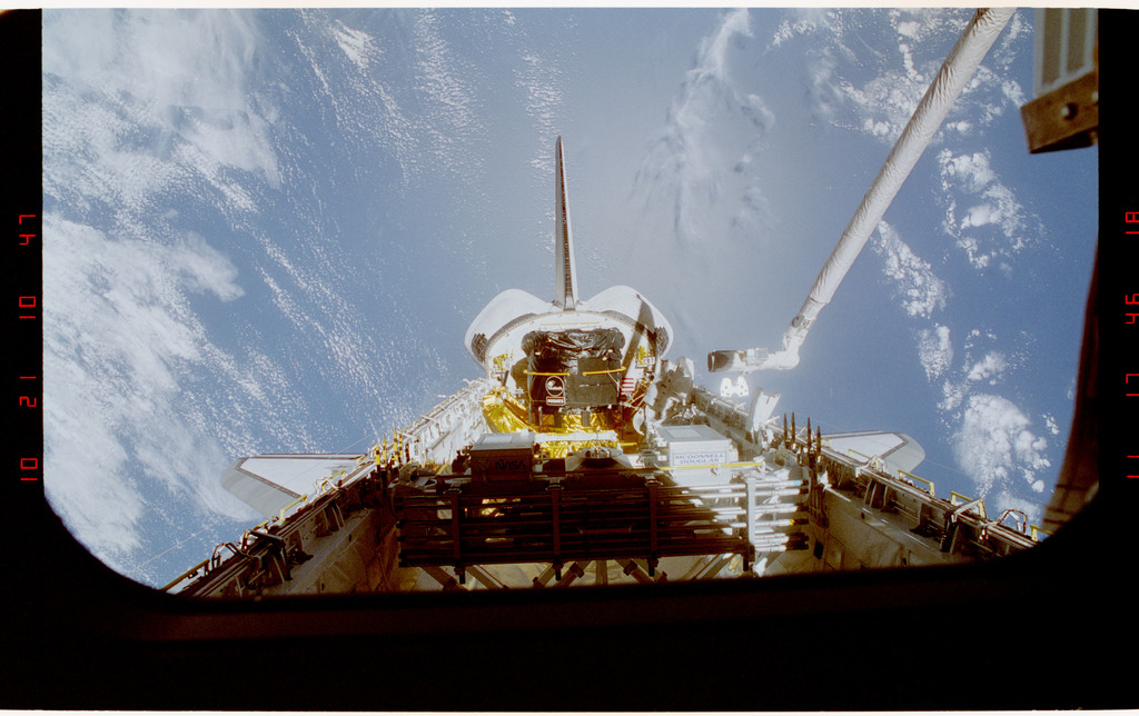 S49-37-009 - STS-049 - Two EVA crewmembers in the payload bay near the new INTELSAT rocket motor.