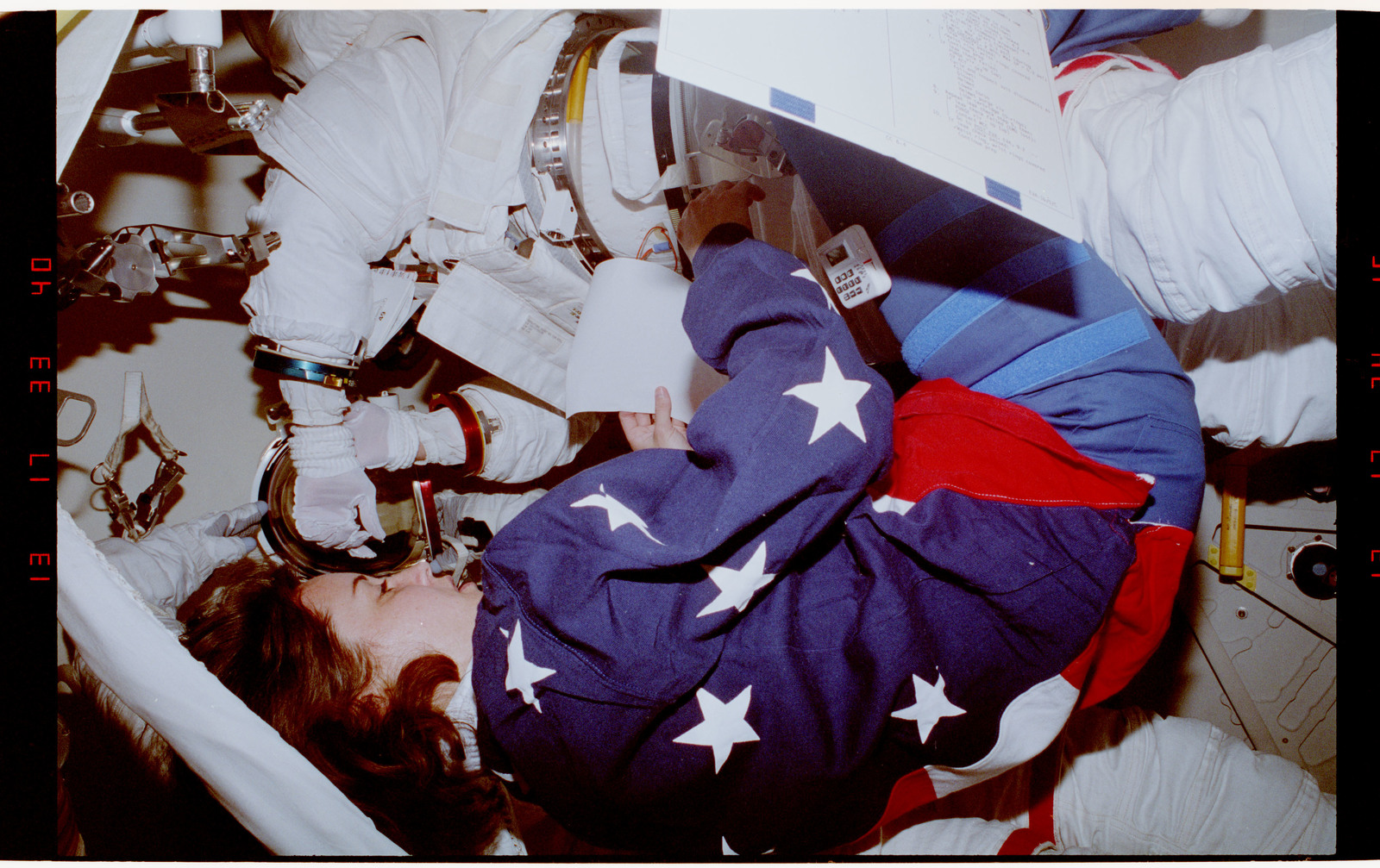S49-39-025 - STS-049 - EVA crewmembers suiting up with the assistance of another crewmember.