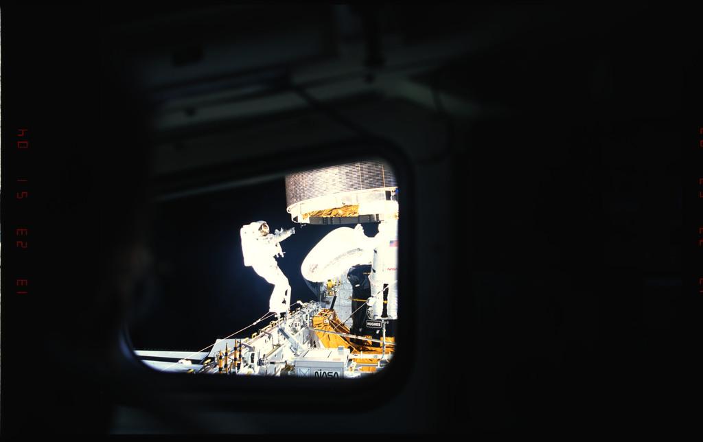 S49-52-018 - STS-049 - Three Mission Specialist EVA manual INTELSAT capture.