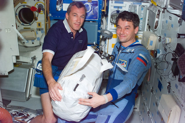 S79E5193 - STS-079 - Astronaut Wilcutt hands water transfer bag to Mir 22 commander on middeck