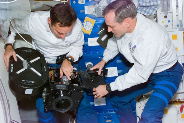 S79E5391 - STS-079 - Astronauts Walz and Akers load film into the IMAX camera