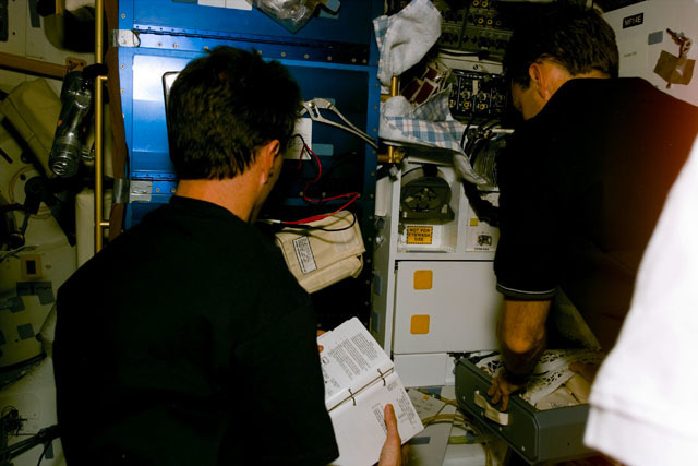 S81E5327 - STS-081 - MS Linenger and pilot Jett unpack items in galley