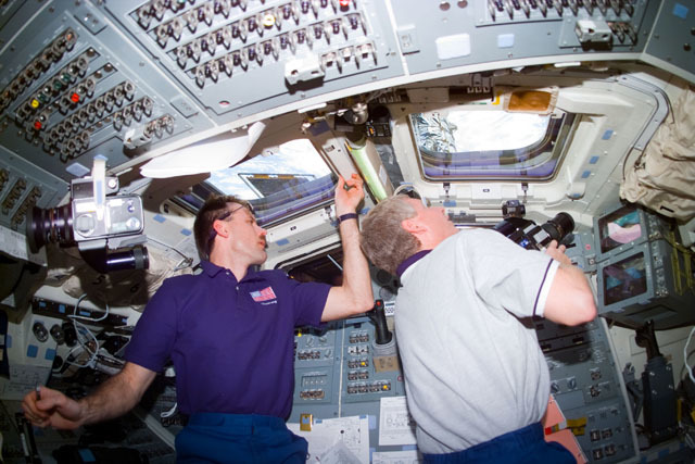 S82E5344 - STS-082 - Steve Hawley and Joe Tanner look out the orbiter windows and take photographs