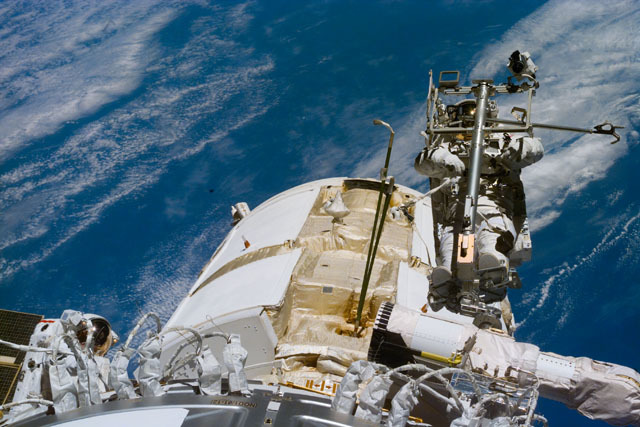 S88E5100 - STS-088 - Newman on RMS arm after deploying TORU antenna on FGB/Zarya module