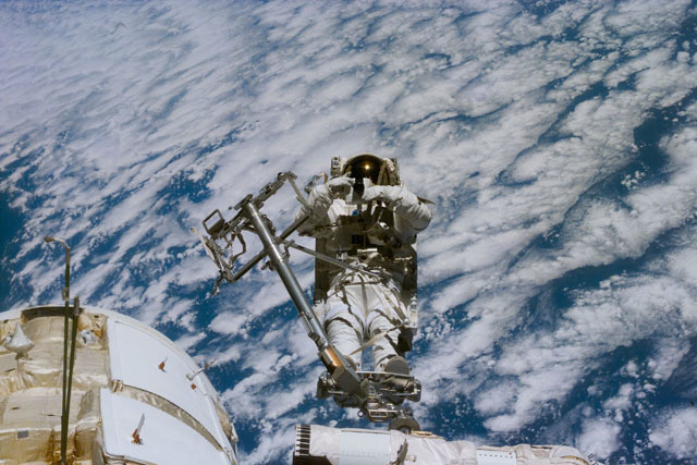 S88E5102 - STS-088 - Newman on RMS arm after deploying TORU antenna on FGB/Zarya module