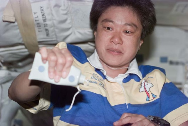 S95E5164 - STS-095 - Candid view of Mukai with tube of toothpaste