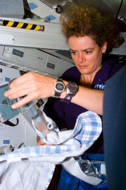 S96E5026 - STS-096 - MS Payette prepares to remove air bubbles from EVA drink packets