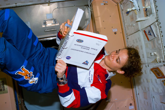 S96E5179 - STS-096 - MS Payette reads ISS Operations Checklist in the Node 1/Unity module