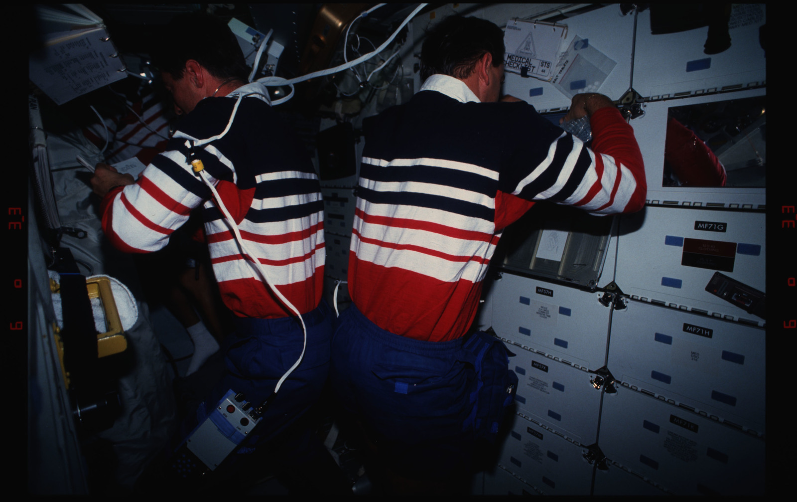 STS044-16-034 - STS-044 - STS-44 Pilot Henricks and PS Hennen work on OV-104's middeck